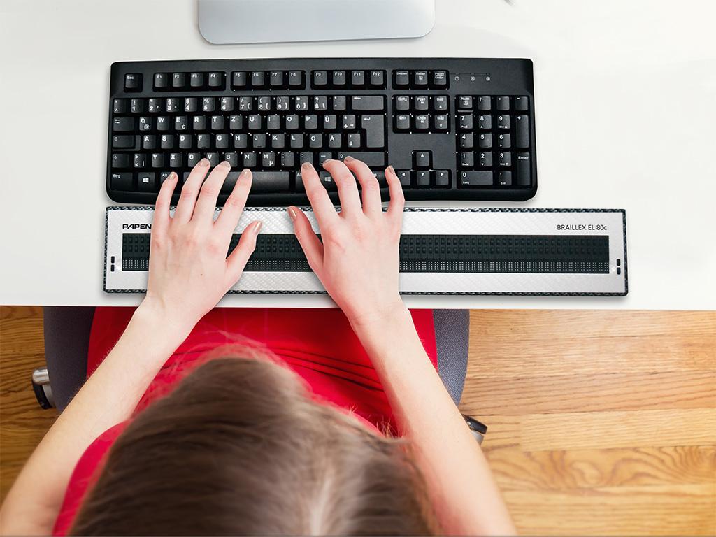 Draufsicht Schreibtisch an dem eine Frau mit einer Braillezeile am PC arbeitet