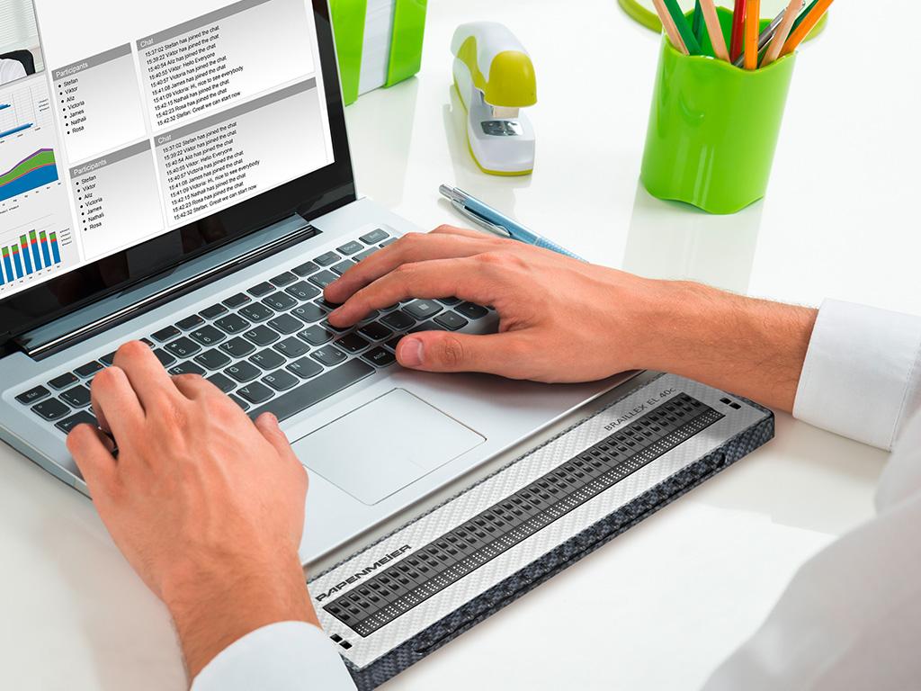 BRAILLEX EL 40c Braillezeile vor  einem Laptop auf dem Hände tippen