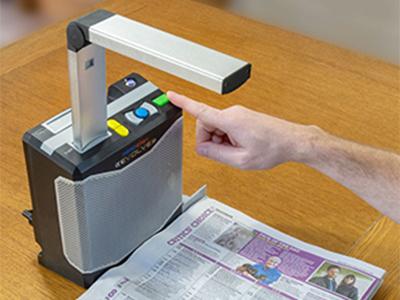 Das eigenständige Lesegerät ReadEasy Evolve wird verwendet, um eine große Zeitungsseite zu erfassen und laut vorzulesen.